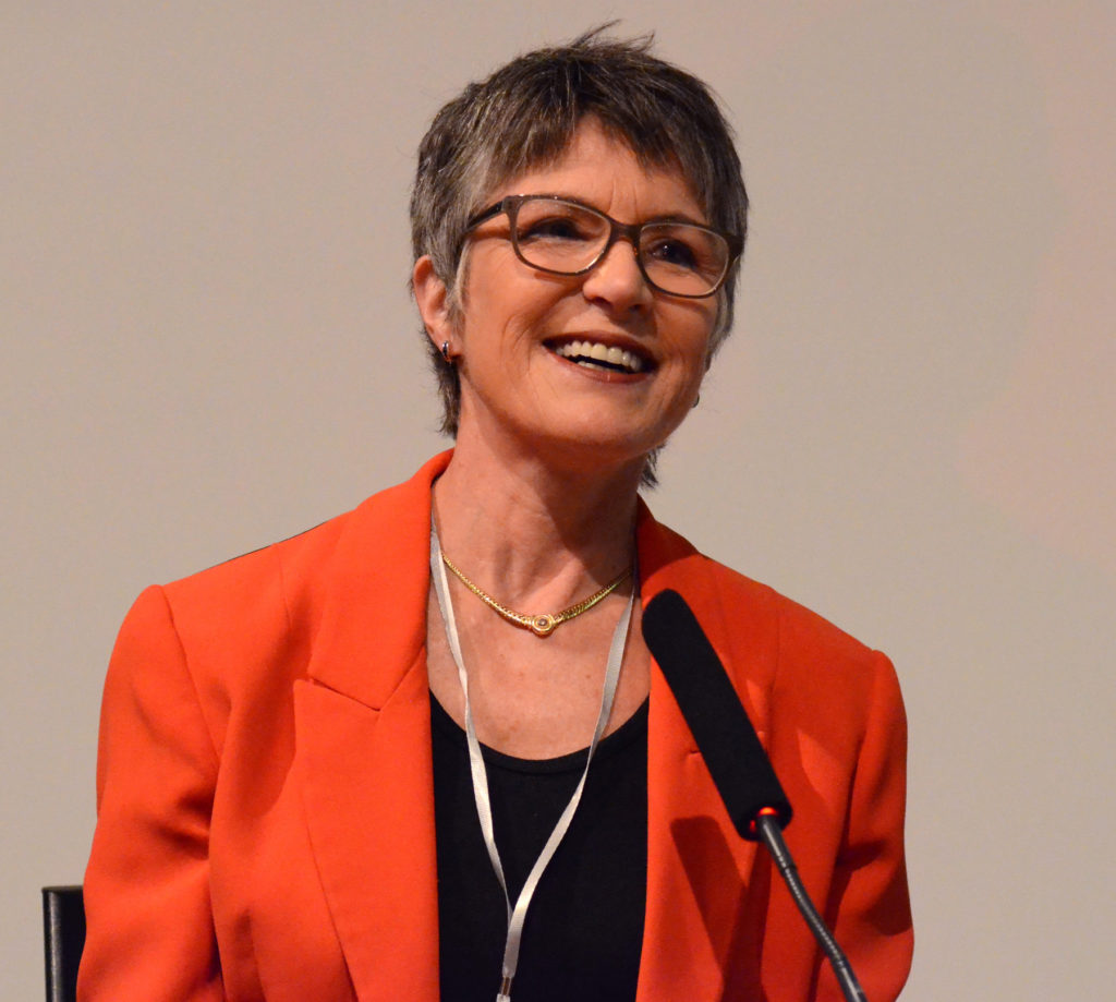 Photograph of Dr Meredith Doig, smiling, wearing red jacket, in front of microphone.