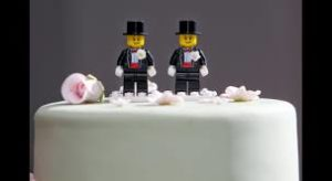 Two male lego figures on top of a wedding cake.